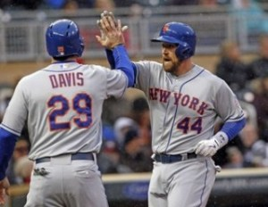 New York Mets John Buck high-fives teammate Ike Davis in game against Twins in Minneapolis