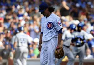 Chicago Cubs starting pitcher Jeff Samardzija (29) walks back to the mound as Los Angeles Dodgers players celebrate after a two-run single by Carl Crawford (25) in the 6th inning at Wrigley Field in Chicago on Saturday, August 3, 2013.